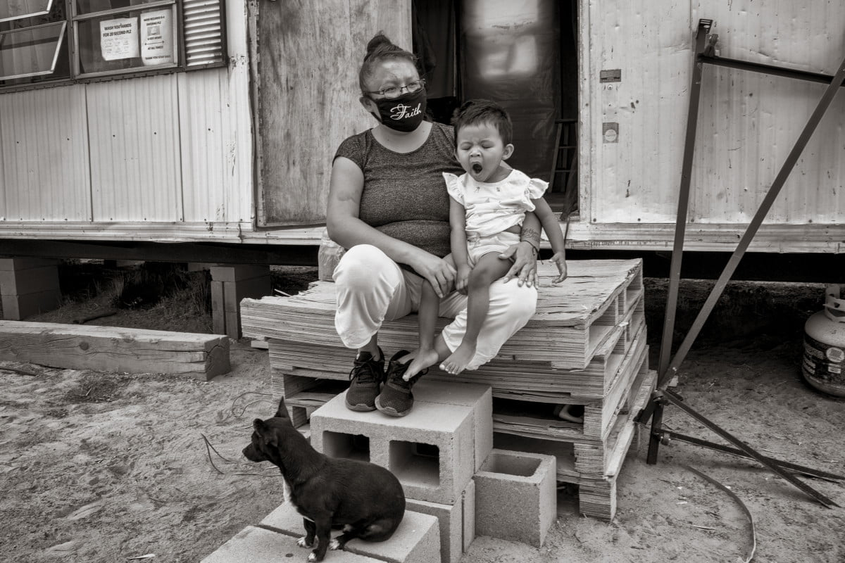 Teresa Smith and her baby, Faith, sit on the porch of their trailer in Borrego Pass.